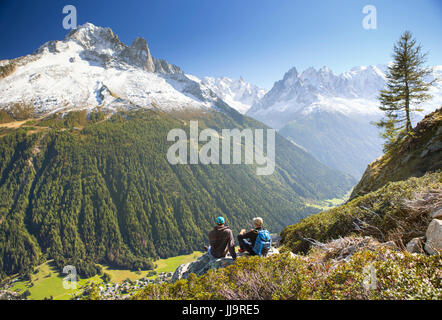 Two hikers are enjoying the view on the Mont Blanc mountains while taking a rest on the Tour du Mont Blanc. They - Stock Photo