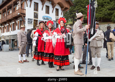 A group of Italian mountain guides are dressed in traditional clothing of the Guide Alpine Courmayeur for a parade - Stock Photo