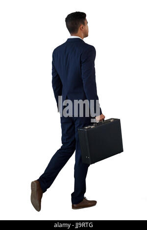 Rear view of businessman walking with briefcase against white background - Stock Photo
