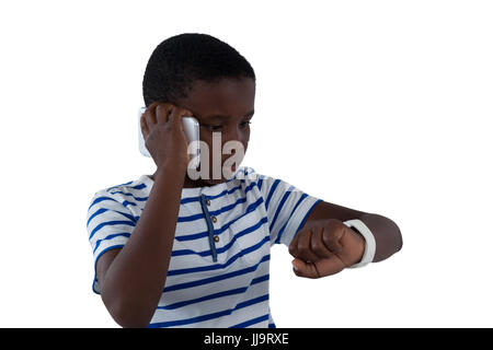 Boy looking at his smart watch while talking on mobile phone against white background - Stock Photo