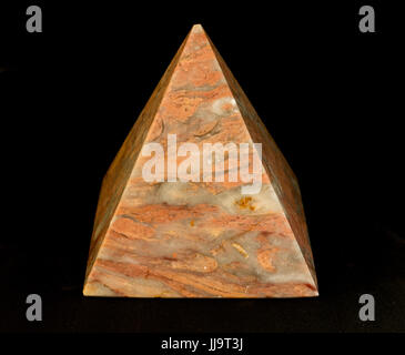 Still life of peach coloured marble pyramid against a black background - Stock Photo