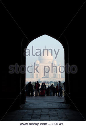 People stand at the entry way to the Taj Mahal in Agra, India. - Stock Photo