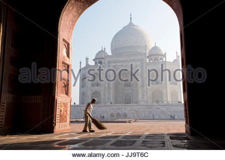 An Indian man sweeping the entry way of the mosque next to the Taj Mahal in Agra, India. - Stock Photo