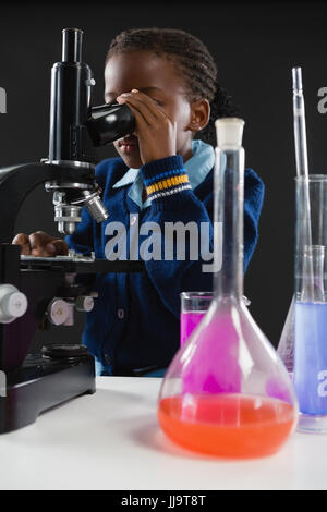 Attentive schoolgirl using microscope against black background - Stock Photo
