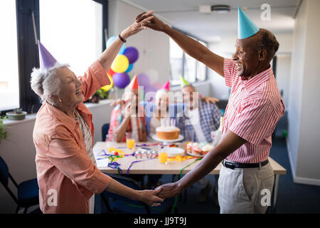 Senior couple making frame against friends by holding hands while enjoying in birthday party