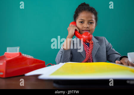 Portrait of businesswoman talking on land line phone while sitting at desk against blue background