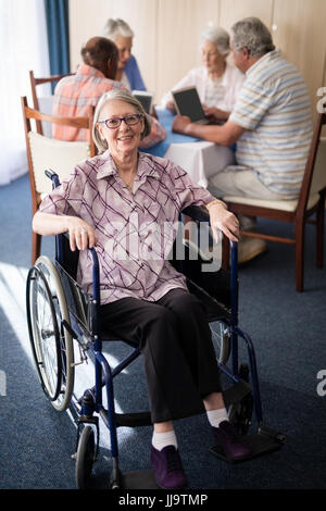 Portrait of smiling disabled senior woman sitting on wheelchair against friends at retirement home - Stock Photo