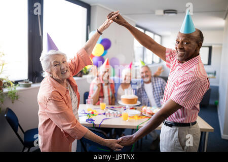 Portrait of smiling senior couple making frame against friends by holding hands while enjoying in birthday party