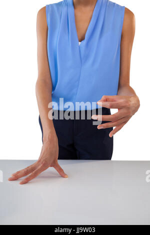 Businesswoman holding something while gesturing at table against white background - Stock Photo