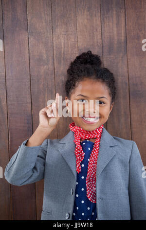 Portrait of businesswoman pointing upwards while standing against wooden wall - Stock Photo