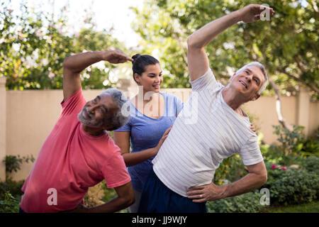Smiling female trainer guiding senior men during exercise at park - Stock Photo