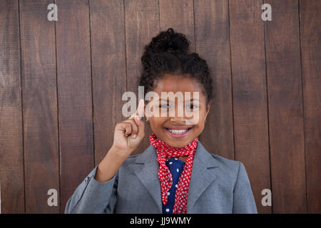 Portrait of smiling businesswoman pointing upwards while standing against wooden wall - Stock Photo