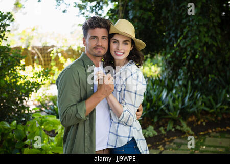 Portrait of happy couple embracing each other in garden - Stock Photo