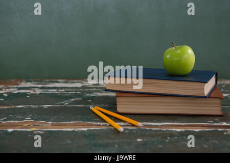 Close-up of apple on stack of books with pencils - Stock Photo