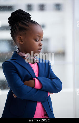 Thoughtful businesswoman with arms crossed standing by window at office - Stock Photo