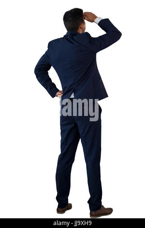 Rear view of businessman shielding eyes while standing against white background - Stock Photo
