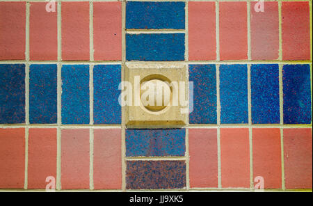red, tan and blue cross pattern on brick wall - Stock Photo