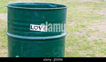 Black and white 'LOVE' bumper sticker on green trash barrel in park - Stock Photo