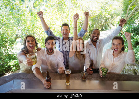 Excited friends at counter in restaurant - Stock Photo