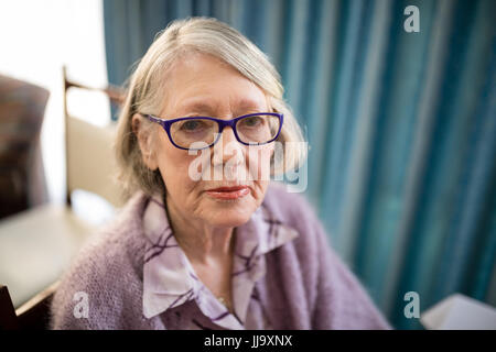 Portrait of senior woman wearing eyeglasses sitting on chair at nursing home - Stock Photo