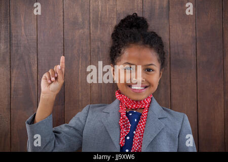 Portrait of happy businesswoman pointing upwards while standing against wooden wall - Stock Photo