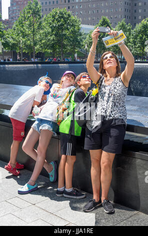 Mother taking a family selfie with her three children at the South Pool of World Trade Center in New York City - Stock Photo