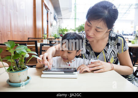 Asian Chinese little girl playing tablet computer with her mother at outdoor cafe - Stock Photo
