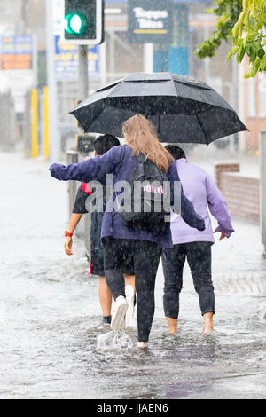 People caught out by torrential rain and flash flooding during a summer storm as they walk through flooded streets - Stock Photo