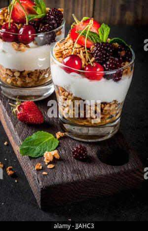 Healthy breakfast. Summer berries and fruits. Homemade Greek yoghurt with granola, blackberries, strawberries, cherries - Stock Photo