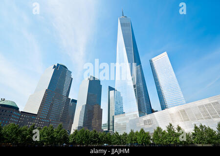 One World Trade Center skyscraper surrounded by glass buildings and green trees, blue sky in New York - Stock Photo