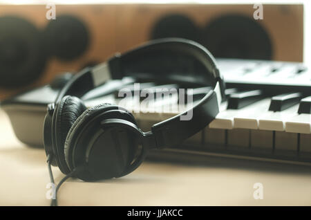 The headphones are on the synthesizer. The synthesizer stands on the background of the speakers. Light photo. Front - Stock Photo