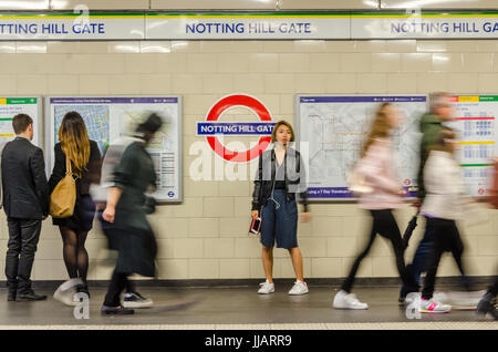 People show as a blur as they walk briskly along the platform at Notting Hill Gate London Underground station. - Stock Photo