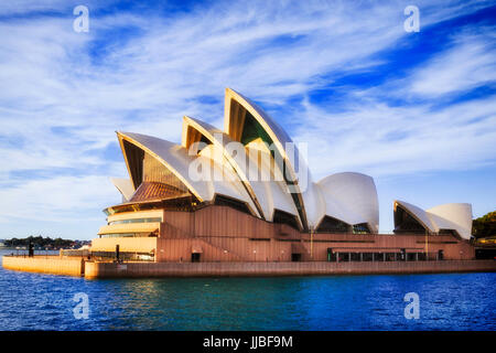 Sydney, Australia - 24 June 2017: Sydney opera house theatre building rising from Sydney harbour waters on a sunny - Stock Photo