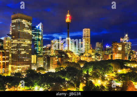 Panorama of Sydney city high-rise towers illuminated at sunset standing over green trees of the central Hyde Park.