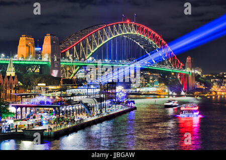 Sydney harbour bridge brightly illuminated and sending blue beams of projector light during Vivid Sydney light and - Stock Photo