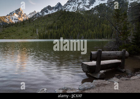 String Lake experiencing a large snow runoff causing the lake to flood areas around a bench. Grand Teton National - Stock Photo