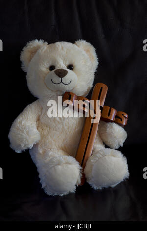 White teddy bear carrying a Jesus cross - Stock Photo