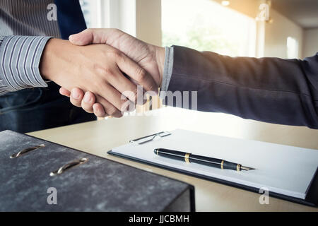 Midsection of a businessman shaking hands with a cropped female interviewer in office. - Stock Photo