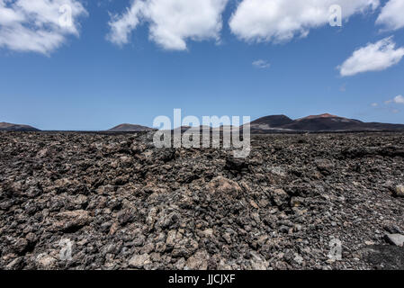Black lava field in the bizarre volcanic landscape of Timanfaya National Park on a sunny day. Lanzarote, Canary - Stock Photo