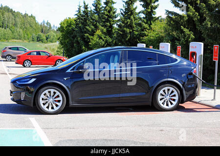 PAIMIO, FINLAND - JULY 14, 2017: The new Tesla Model X electric car is being charged at Tesla Supercharger. The - Stock Photo