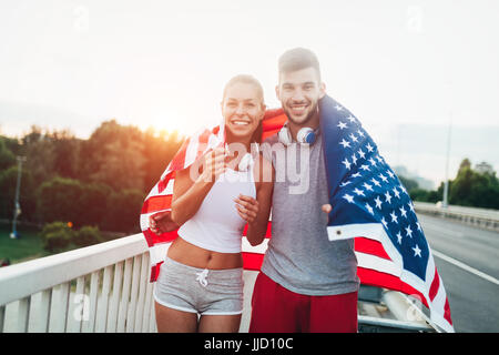 Portrait of attractive fitness couple holding American flag - Stock Photo
