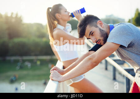 Portrait of man and woman during break of jogging - Stock Photo