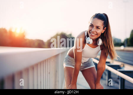 Portrait of woman taking break from jogging - Stock Photo
