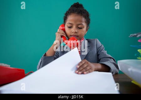 Businesswoman checking file while talking on land line at desk against blue background