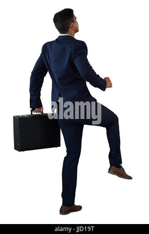 Rear view of businessman with briefcase climbing invisible steps against white background - Stock Photo