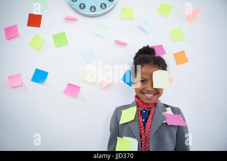 Smiling businesswoman with sticky notes stuck on suit and head standing against wall - Stock Photo