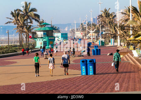 DURBAN, SOUTH AFRICA - JULY 7, 2017: Early morning view of many unknown pedestrians and cyclists on paved promenade - Stock Photo