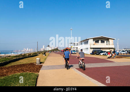 DURBAN, SOUTH AFRICA - JULY 15, 2017: Early morning view of many unknown pedestrians and cyclists on paved promenade - Stock Photo