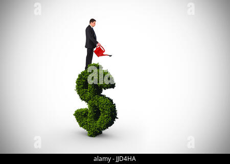 Businessman holding red watering can against dollar sign made of leaves - Stock Photo