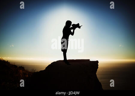 Silhouette businesswoman holding megaphone  against scenic view of mountain by sea against sky - Stock Photo